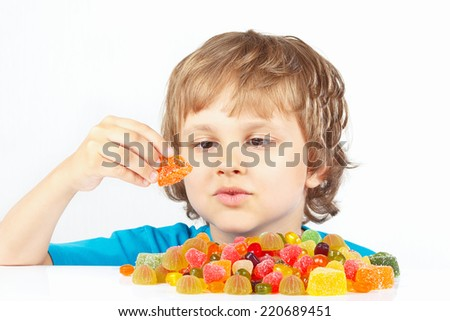 Little blonde boy with jelly candies on a white background