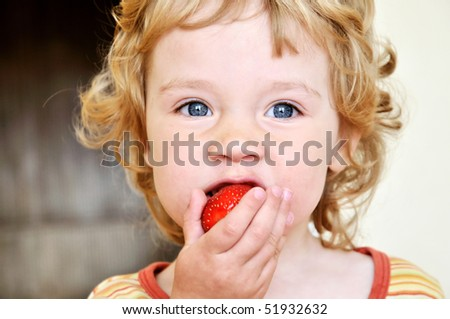 little blonde curly girl eating fresh strawberry - stock photo