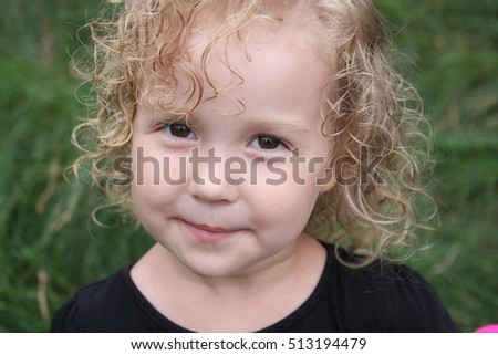 Little blonde curly girl with big beautiful eyes