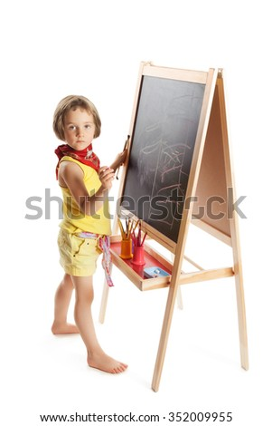 Little blonde girl drawing with chalk on a blackboard - Isolated on white background