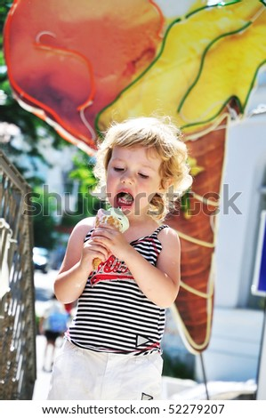 little blonde girl happily eating big ice cream cone - stock photo