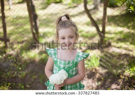 Little blonde girl in a green dress and with flowers in the hands in the summer garden