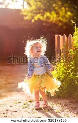 little blonde girl in a tutu skirt standing on the street in the - stock photo