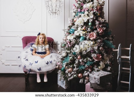 Little blonde girl in beautiful dress waiting for gifts sitting near Christmas tree at home - stock photo