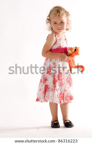 Little blonde girl in fashionable dress and soft toy in the hand /Small child with stuffed animal