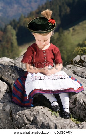 Little blonde girl in typical Bavarian costume on the mountain and pray /