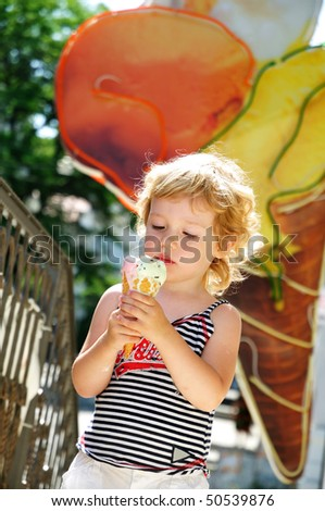 little blonde girl looking with  gladness at the big ice cream - stock photo