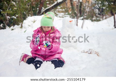 Little blonde girl playing with snowflakes in the deep snow in Jerusalem - stock photo