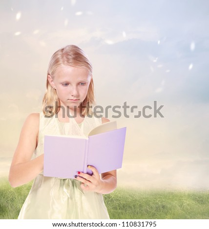 Little Blonde Girl Reading a Book in the field - stock photo