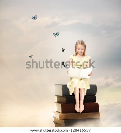 Little Blonde Girl Reading a Book  on Top of Books - stock photo
