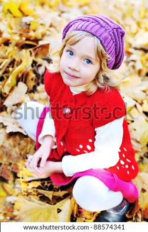little blonde girl sitting in foliage - stock photo