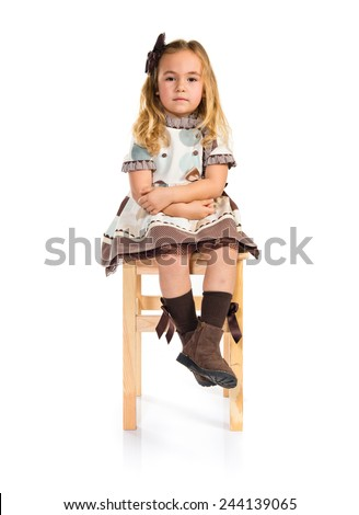 Little blonde girl sitting on chair
