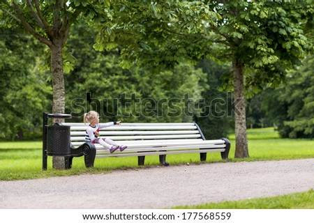 Little blonde girl sitting on the bench in the summer park looking to her side - stock photo