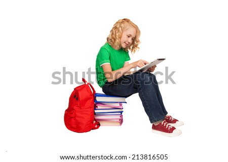 little blonde girl sitting on the floor near books and bag holding tablet  - stock photo