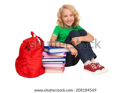 little blonde girl sitting on the floor near books and bag over white background - stock photo