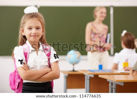 Little blonde girl studying at school class - stock photo