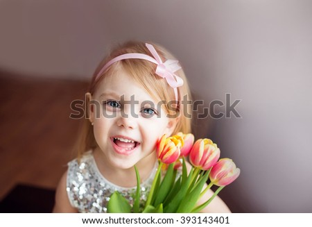 Little blonde girl with a bouquet of tulips., pressed to the colors in a white dress with a ribbon in her hair, horizontal image, look at the camera, with a cheerful smile - stock photo