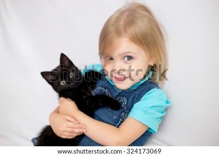 little blonde girl with pigtails in a blue shirt on a white sofa with a black kitten looking into the camera and smiling.  - stock photo