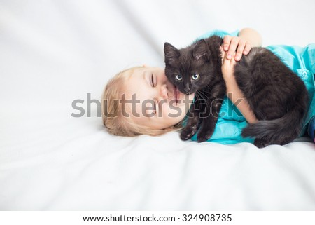 little blonde girl with pigtails in a blue shirt on a white sofa with a black kitten looking into the camera and smiling - stock photo