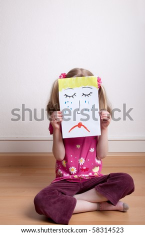 Little blonde girls holding sad face mask - stock photo