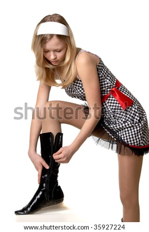little blonde in a dress in a cage and lacquer boots on a light background