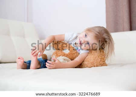little blonde nice smiling girl three years sitting with a soft toy dog on a white leather couch - stock photo