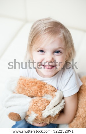 little blonde smiling girl three years sitting with a soft toy dog on a white leather couch - stock photo