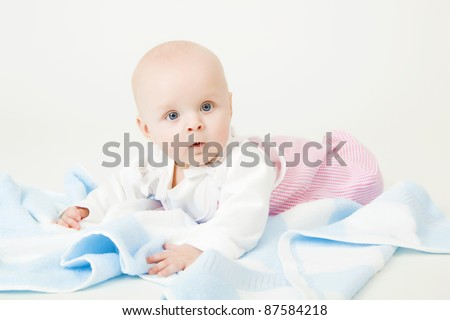 little blue-eyed girl with a blue towel. baby. Studio photography