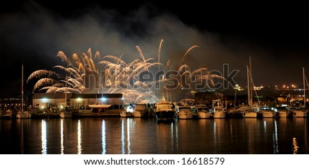 Little boats illuminated by golden fireworks