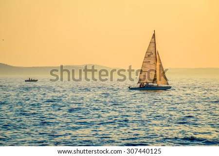 Little boats sailing at sunset, with island silhouettes in the background, on the Adriatic sea, Croatia, Mediterranean.