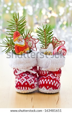 Little boots filled with sweets for christmas - stock photo