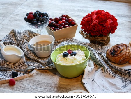 Little bowl of fresh farmer cream cheese with cranberries, jam, yoghurt and fresh pastry