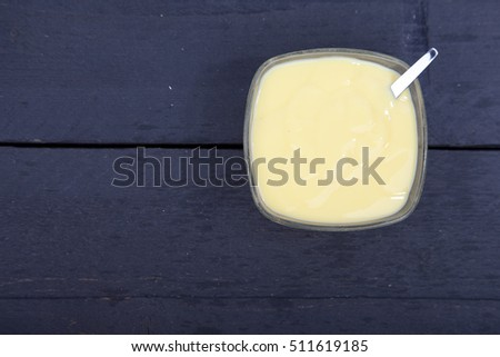 Little bowl of vanilla custard on wooden background