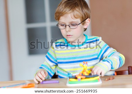 Little boy, adorable creative kid boy with glasses playing with dough, colorful modeling compound, sitting at table at home or kindergarden, nursery. Creative leisure with kids. - stock photo