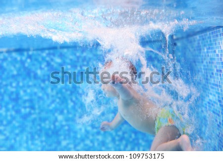 Little boy after diving into a swimming pool, hand and water bubbles in focus - stock photo