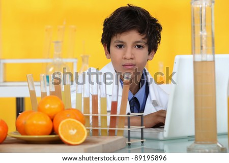 little boy analyzing oranges in the laboratory - stock photo