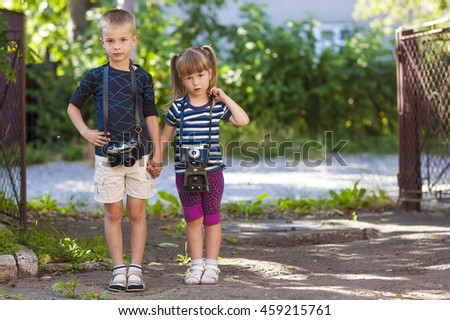 Little boy and a little girl wit two vintage cameras standing together holding hands