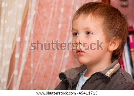 Little boy and a shelf with books, focus on the child