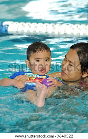 Little boy and asian mother playing in swimming pool