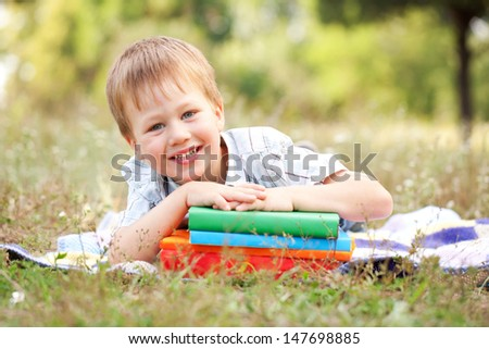 Little boy and books outdoors. Back to school. Summer holiday. - stock photo