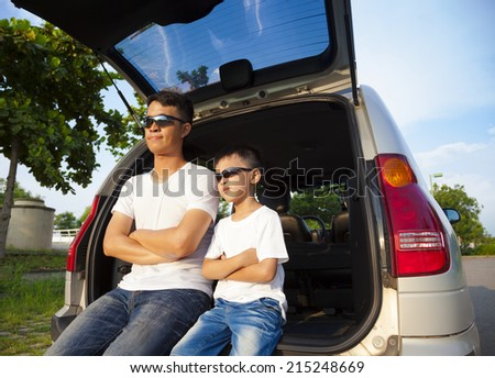 little boy and father sitting on their car in the park