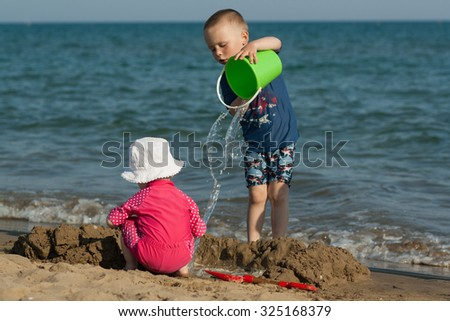 little boy and girl are playing on sand beach. Brother and sister are playing with water and beach toys. Dressed in UV protection swimming suits and summer white hat. Wet sand, small waves.   - stock photo
