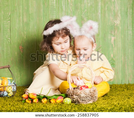 Little boy and girl as a Easter rabbits on the grass with colorful eggs - stock photo