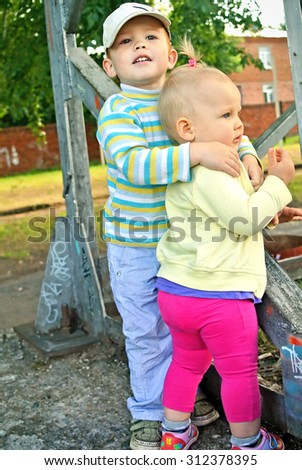 Little boy and girl, brother and sister are embracing, on the walk - stock photo