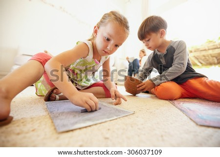 Little boy and girl coloring pictures with chalk colors while sitting on floor in living room at home.