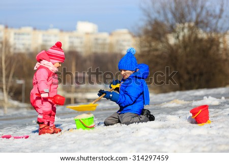 little boy and girl digging snow in winter, kids winter activities - stock photo