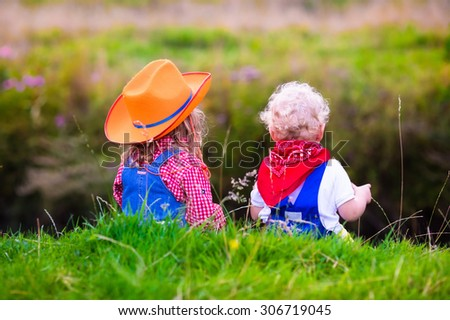 Little boy and girl dressed up as cowboy and cowgirl playing with toy rocking horse in park. Kids play outdoors. Children in Halloween costumes at trick or treat. Toys for preschooler or toddler child - stock photo