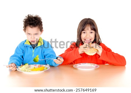 little boy and girl eating hamburguer and vegetables isolated in white background