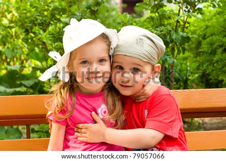 little boy and girl embrace in summer park