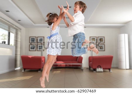 Little boy and girl happily jumping on a home interior - stock photo